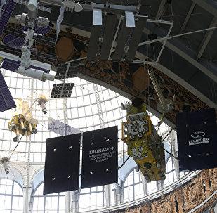 نموذج بالحجم الكامل للمركبة الفضائية Glonass-K (في الخلفية) لنظام الملاحة العالمي غلوناس الروسي في معرض مركز رواد الفضاء والطيران