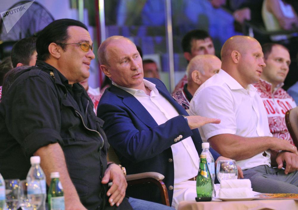 الرئيس الروسي فلاديمير بوتين والممثل الأمريكي ستيفين سيغال أثناء حضورهما لمباراة بطولة روسيا للفنون القتالية المختلطة، 11 أغسطس/ آب 2012