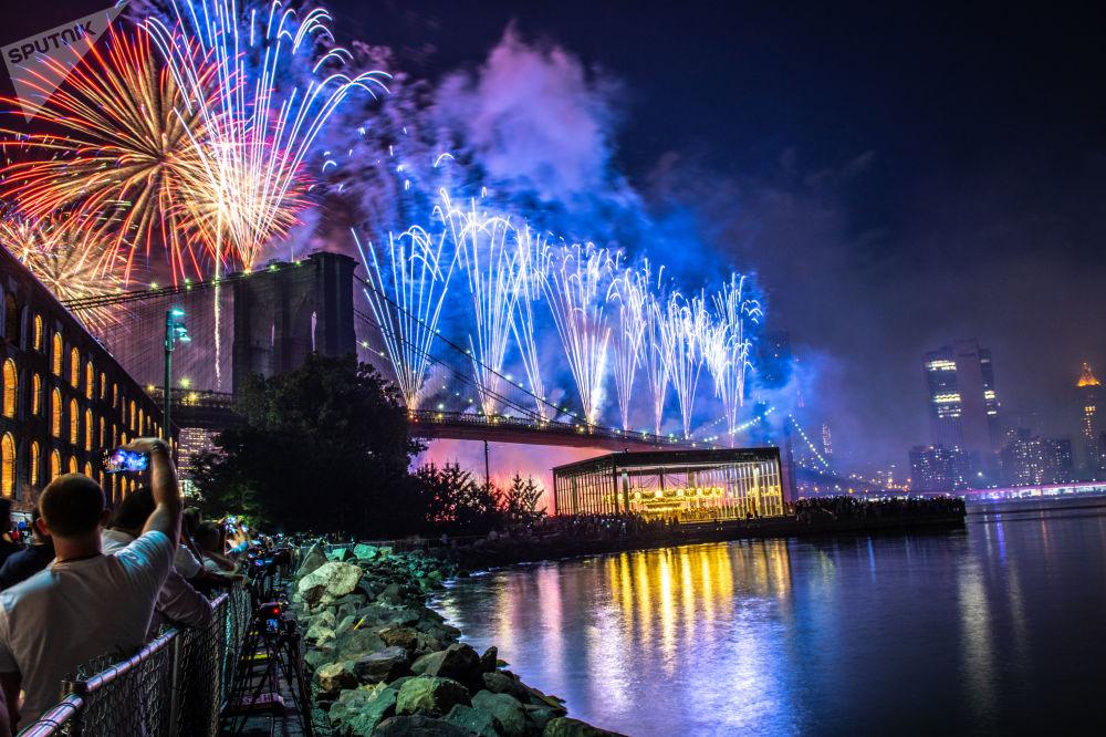 أمريكيون يشاهدون الألعاب النارية فوق جسر بروكلين في نيويورك خلال احتفالات يوم الاستقلال الأمريكي.