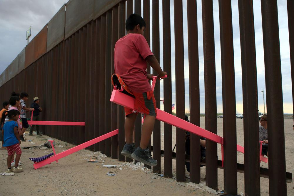 العائلات الأمريكية والمكسيكية تلعب لعبة تسمى صعودًا وهبوطًا (تأرجح الأرجوحة) عبر الحدود المكسيكية مع الولايات المتحدة في منطقة أنابرا في سيوداد خواريز، ولاية تشيهواهوا، المكسيك في 28 يوليو/ حزيران 2019
