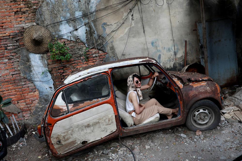 امرأة تلتقط صورة في سيارة قديمة في الشارع كمنطقة جذب سياحي، في بانكوك، تايلاند في 29 يوليو/ تموز 2019.