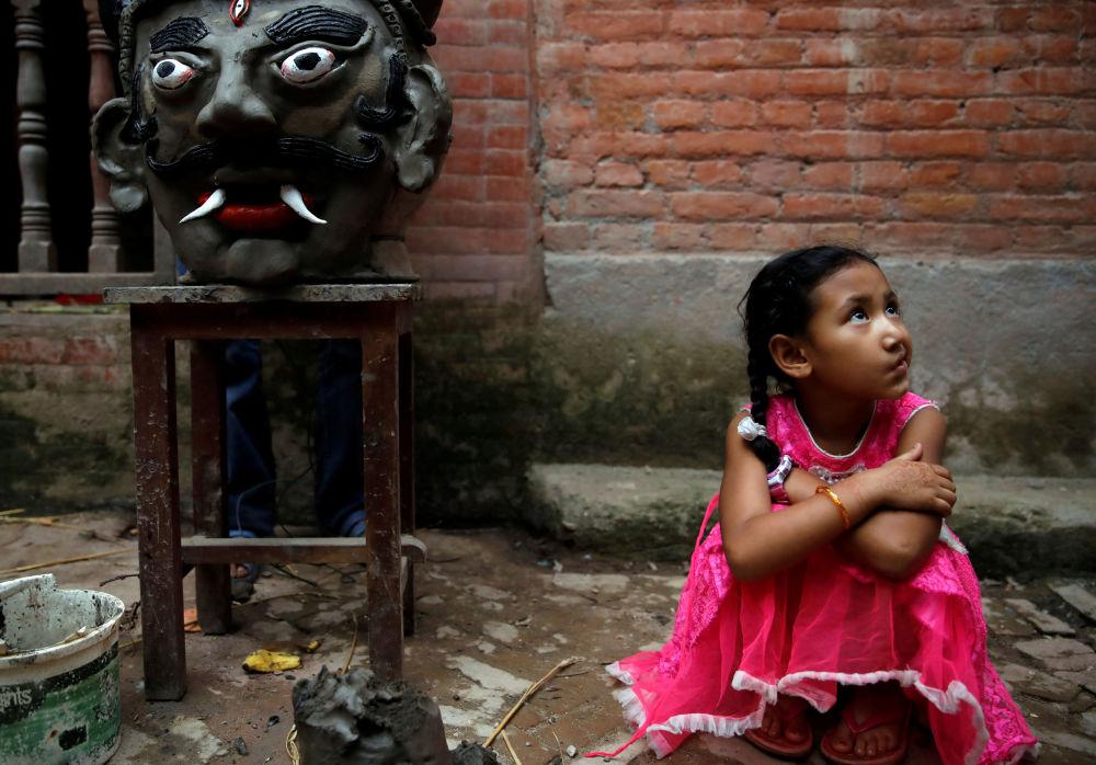 فتاة جالسة بجوار رأس تمثال شيطان غانتاكارن في مهرجان غنتاكارنا في نيبال، 30 يوليو/ تموز 2019