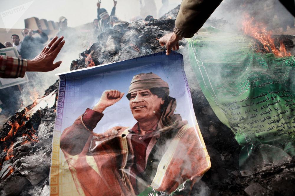 أهالي بنغازي يحرقون صوراً لمعمر القذافي، وملصقات تحمل اقتباسات من الكتاب الأخضر للقذافي. بنغازي، ليبيا 02.03.2011