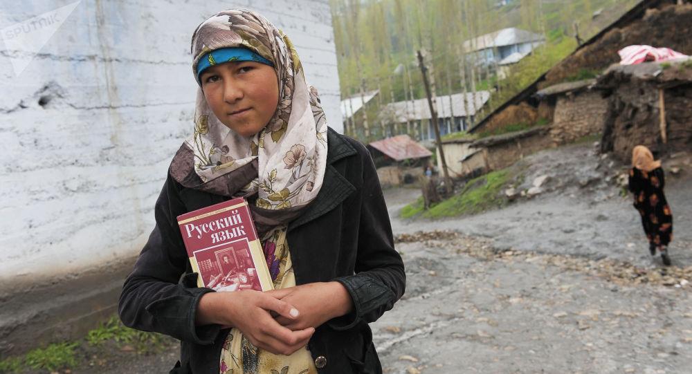 فتاة في طاجيكستان تحمل كتاب اللغة الروسية
