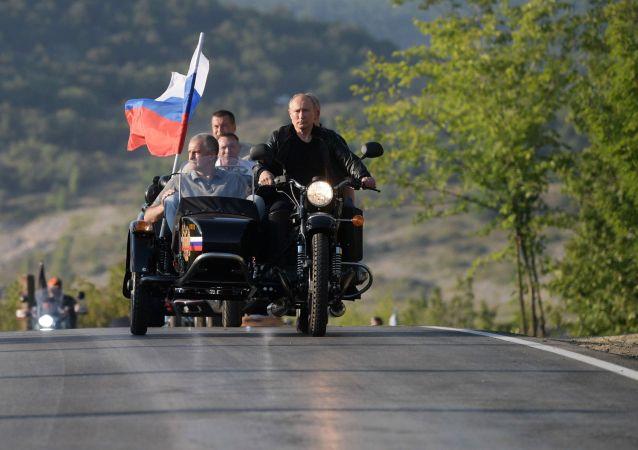 الرئيس الروسي فلاديمير بوتين يشارك في مسيرة للدراجات النارية الذئاب الليلية التي ينظمها نادي الدراجات النارية الذئاب الليلية (نوتشنيه فولكي) في سيفاستوبول يقود دراجة نارية من طراز أورال مع مركبة