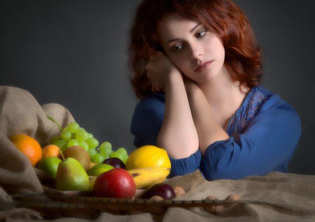 امرأة تنظر إلى طبق الفواكه