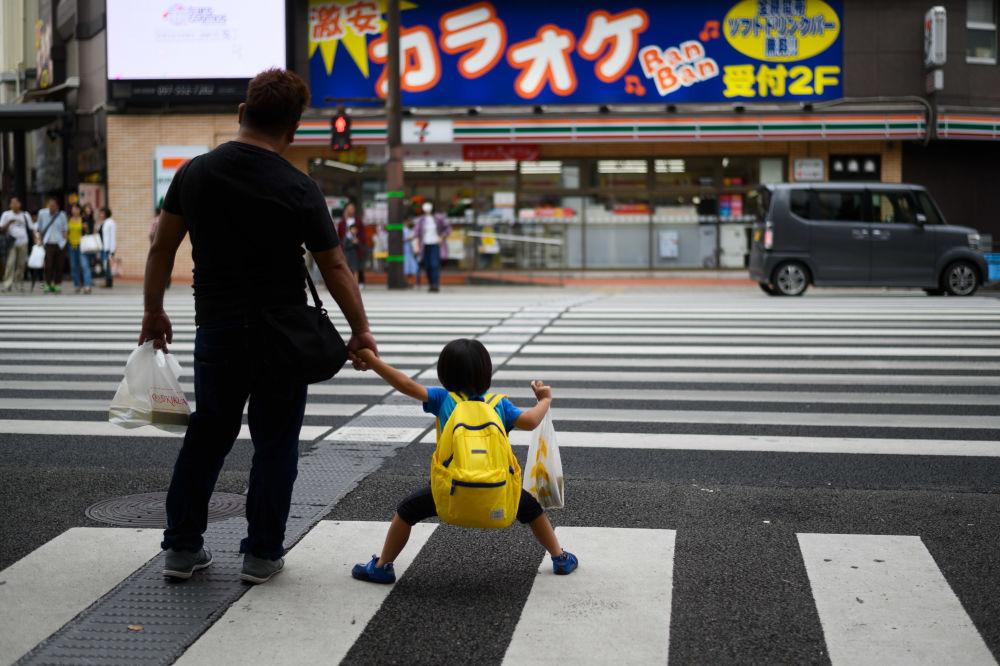 رجل وابنه ينتظران إشارة المرور لعبور الشارع في مدينة أويتي، اليابان 21 سبتمبر 2019