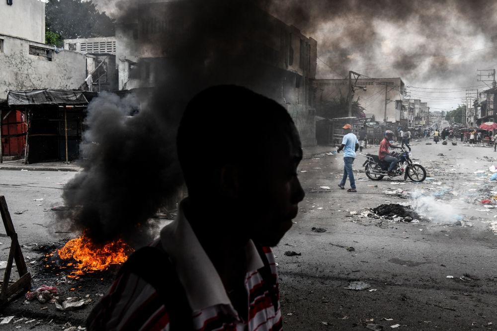 رجل يسير بجوار إطارات محترقة أثناء احتجاجات في بورت أو برنس، هايتي 25 سبتمبر 2019