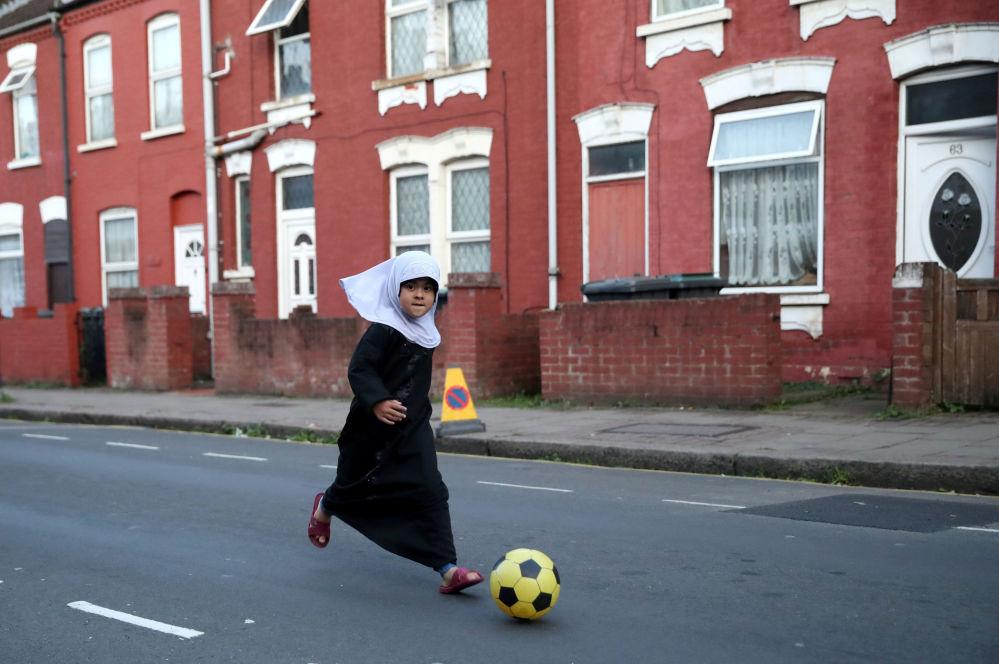 طفلة تلعب بالكرة في إحدى شوارع مدينة لندن البريطانية