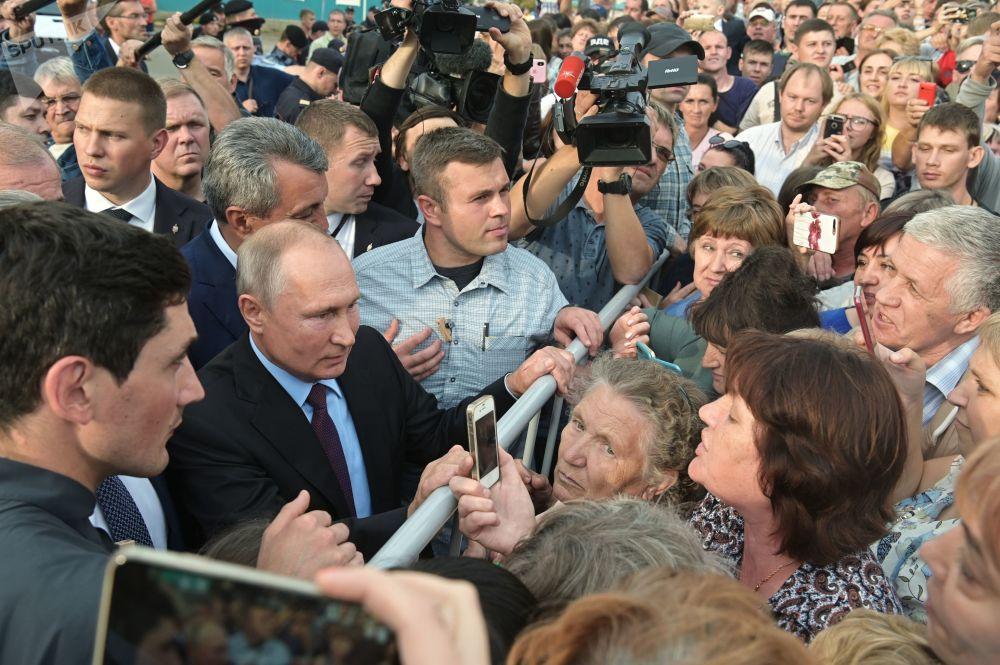 الرئيس الروسي فلاديمير بوتين يتحدث مع السكان المحليين بعد زيارة مدرسة الثانوية رقم 6 في مدينة تولون، إقليم سيبيريا