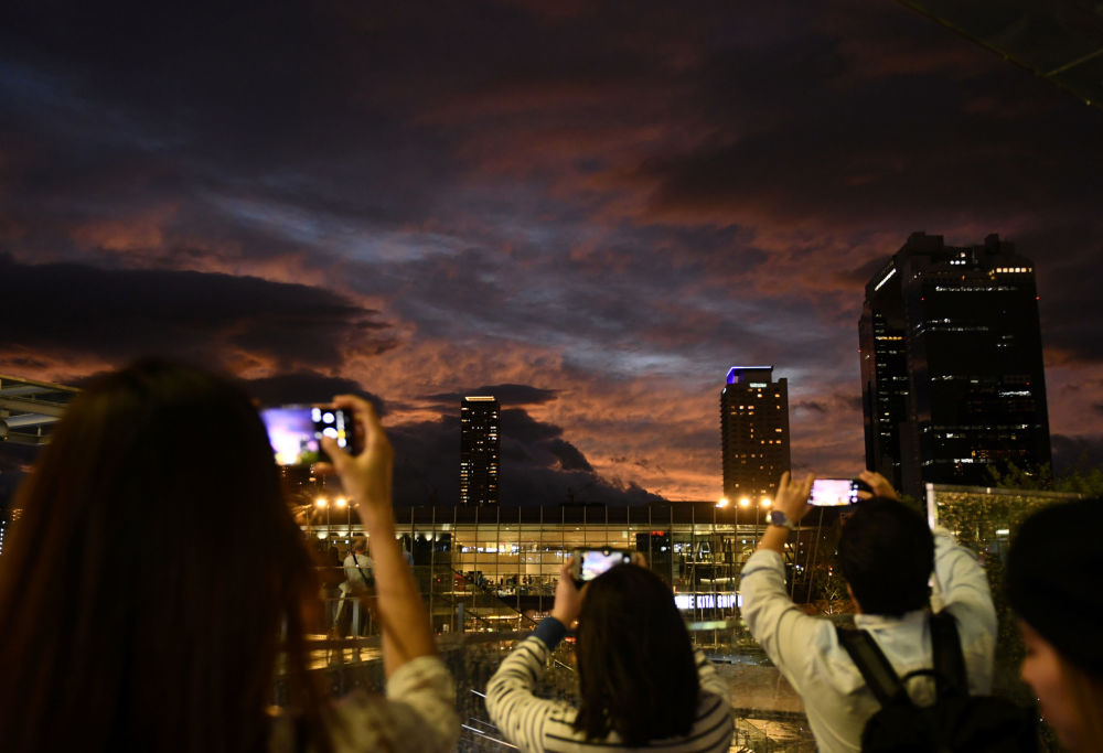مواطنون يلتقطون صور للسماء غروب الشمس أثناء اقتراب الاعصار هاغيبيس في أوساكا، اليابان 12 أكتوبر 2019