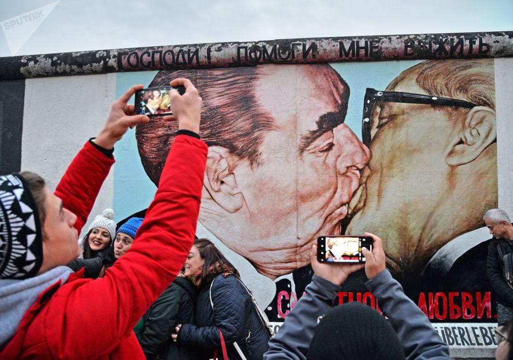 جدارية - رسم غرافيتي للزعينم السوفيتي بريجنيف وقائد جمهورية ألمانيا الديمقراطية (ألمانيا الشرقية) إريش هونيكر على الجزء المتبقى من جدار برلين (East-Side Gallery)، حيث يتجمع المواطنون والسياح بمناسبة مرور الذكرى الـ 30 لإسقاط الجدار.
