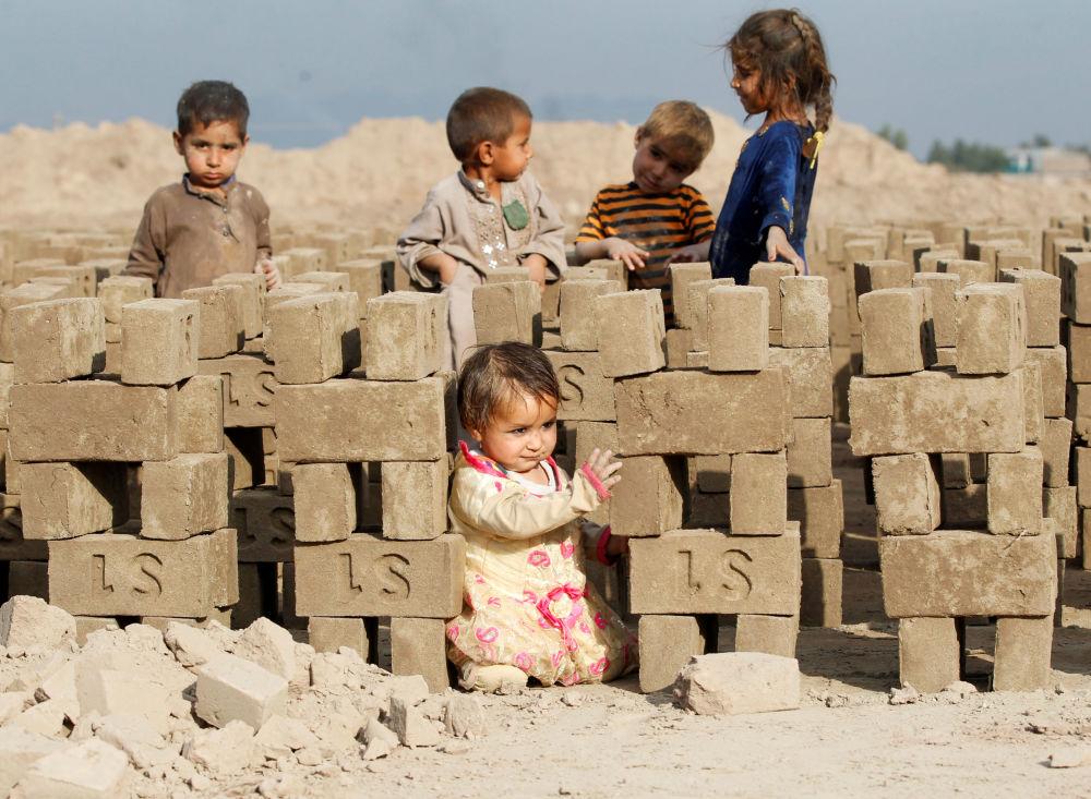 أطفال أفغانيون يلعبون في مصنع لصناعة الطوب على مشارف مدينة جلال آباد، أفغانستان 13 نوفمبر 2019