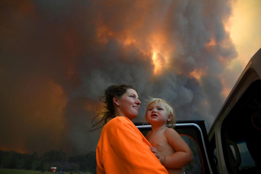 امرأة وطفلتها تنظران إلى الدخان الكثيف المتصاعد من حرائق الغابات بالقرب من منطقة نانا غلين، بالقرب من ميناء كوفس، أستراليا، 12 نوفمبر 2019