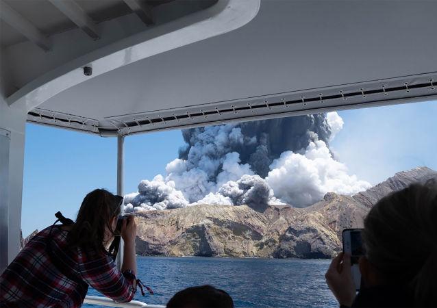 سياح يلتقطون صور لثوران بركان على جزيرة وايت آيلند في نيوزيلندا، 9 ديسمبر 2019