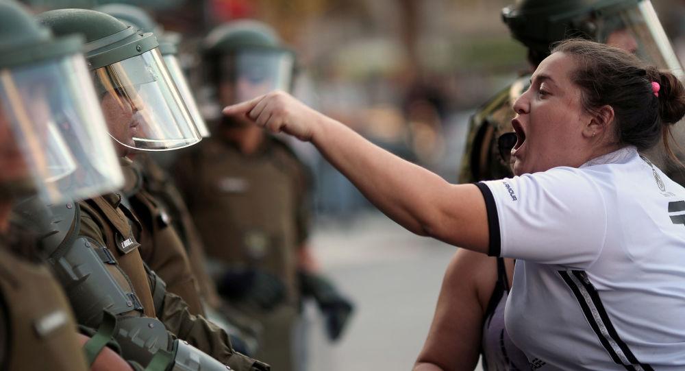 امرأة تصرخ على شرطي خلال احتجاجات مناهضة للحكومة في سانتياغو، تشيلي 15 ديسمبر 2019