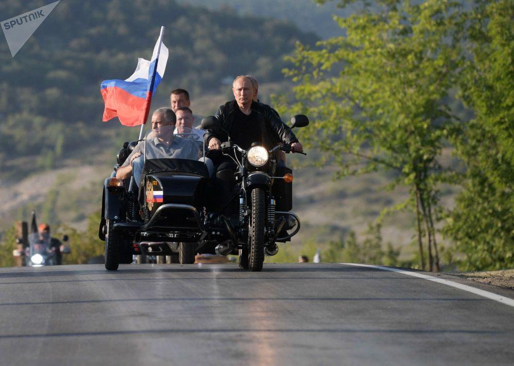 الرئيس الروسي فلاديمير بوتين يشارك في مسيرة للدراجات النارية الذئاب الليلية التي ينظمها نادي الدراجات النارية الذئاب الليلية (نوتشنيه فولكي) في سيفاستوبول يقود دراجة نارية من طراز أورال مع مركبة، 10 أغسطس 2019
