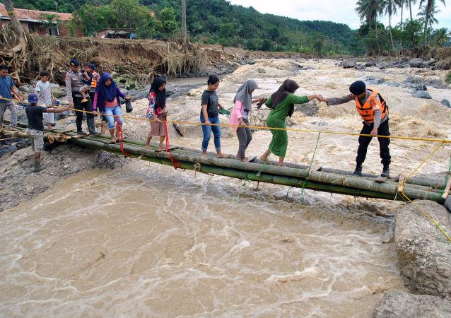 الشرطة تساعد سكان مدينة بوكور في إندونيسيا بعبور جسر الطوارئ