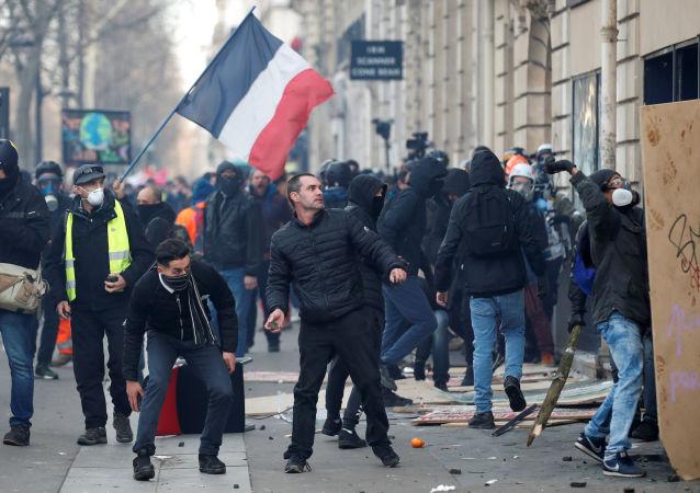 متظاهر يحمل حجرا خلال مظاهرة لأعضاء النقابات العمالية والعمال الفرنسيين، 11 يناير/ كانون الثاني 2020