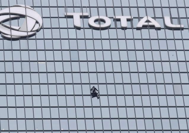 الرجل العنكبوت الفرنسي، ألان روبير، يتسلق برج توتال، في العاصمة الفرنسية باريس، تضامنا مع عمال محتجين على إصلاح نظام معاشات التقاعد، 13 يناير/ كانون الثاني 2020