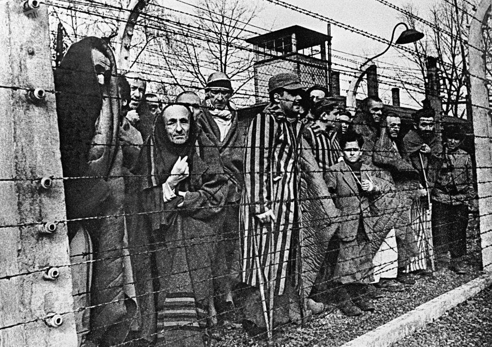سجناء معسكر أوشفينتز ينظرون إلى الكاميرا من وراء الأسلاك الشائكة. صورة للذكرى - للمصور ب. بوريسوف بعنوان أوشفينتزيزم من سلسلة الصور البشرية لن تنسى، لن تغفر.