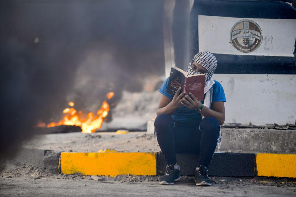 أحد المتظاهرين يقرأ كتبا خلال الاحتجاجات في النجف، العراق 19 يناير 2020